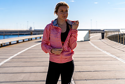 Female athlete unzipping jacket while standing on boardwalk - p300m2273591 by Albert Martínez