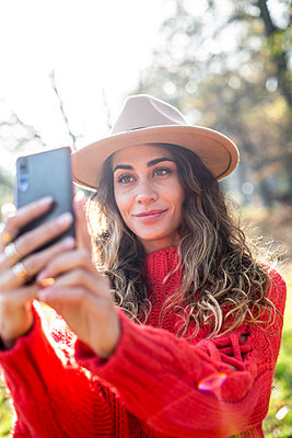 Young woman in red jumper takes a selfie - p975m2222119 by Hayden Verry