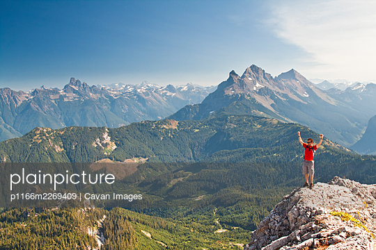 Hiker reaches summit of mountain, celebrates with arms raised. - p1166m2269409 by Cavan Images