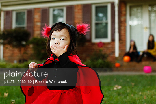 Girl dressed as ladybird with hand on mouth - p1427m2283180 by Roberto Westbrook