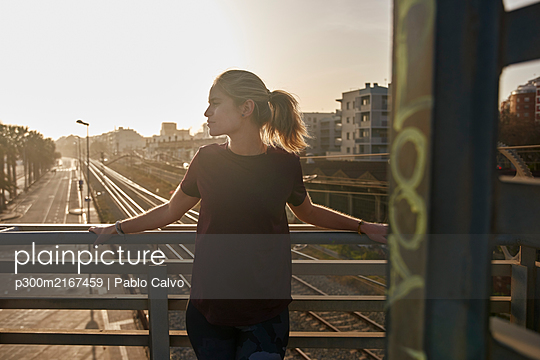 Sporty young woman standing on a bridge at sunset - p300m2167459 by Pablo Calvo
