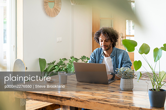 Male entrepreneur working on laptop at home - p300m2276550 by Steve Brookland