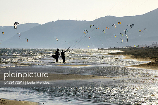 Couple flying kites on beach - p42917291f by Leila Mendez