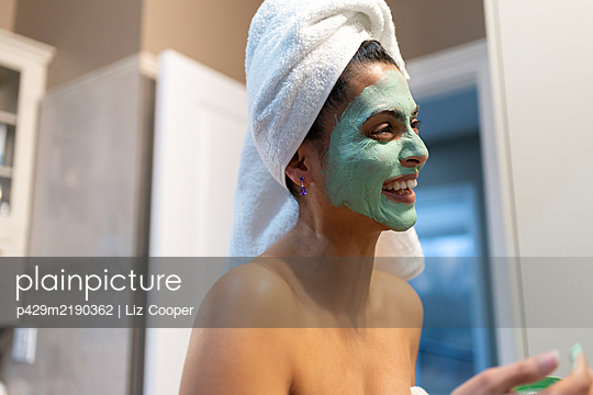 Woman standing in bathroom, applying face mask after bath. - p429m2190362 by Liz Cooper