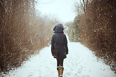 Rear view of woman walking on snowy field - p1166m1209569 by Cavan Images