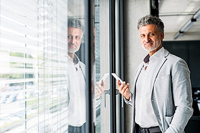Portrait of smiling mature businessman at the window in office holding cell phone - p300m1536005 by HalfPoint