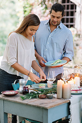 Couple preparing a romantic candelight meal outdoors - p300m2068345 by Alberto Bogo