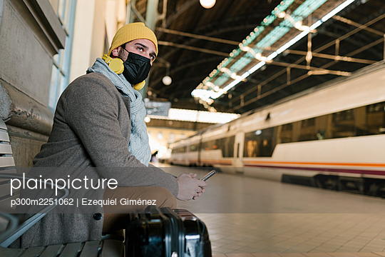 Man wearing protective face mask using mobile phone while sitting on bench at station - p300m2251062 by Ezequiel Giménez