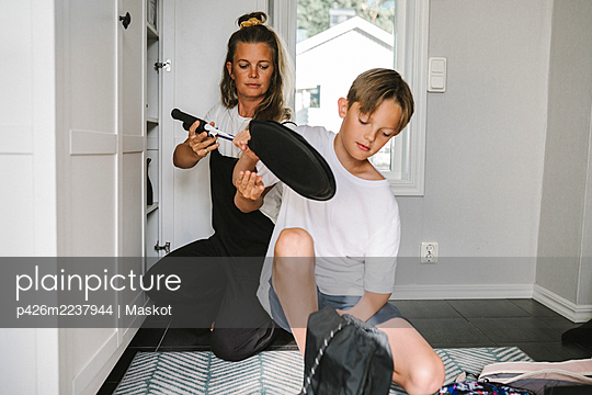 Mother and son holding badminton at home - p426m2237944 by Maskot
