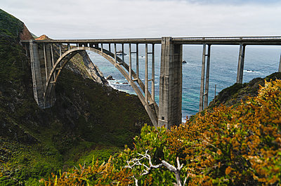 Arch bridge over mountains by sea - p1166m1194024 by Cavan Images