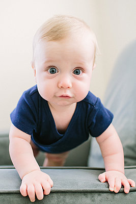 Baby staring ointo camera with wide eyes - p1166m2191797 by Cavan Images