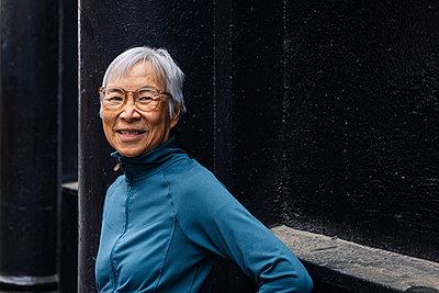 Smiling senior woman wearing eyeglasses standing by black wall - p1166m2285594 by Cavan Images