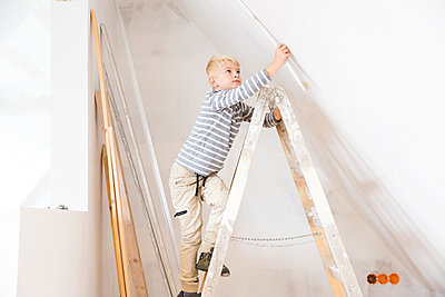 Boy with pocket rule on ladder measuring wall in attic to be renovated - p300m2083645 by Michelle Fraikin