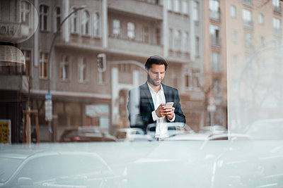 Male entrepreneur using mobile phone while standing by window - p300m2287465 by Gustafsson