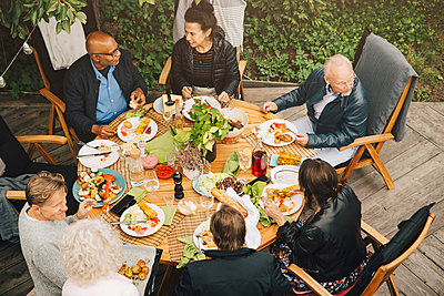 High angle view of senior friends enjoying meal at dining table during garden party at back yard - p426m2194905 by Maskot