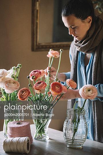 Woman arranging fresh flowers - p300m2005701 von Alberto Bogo