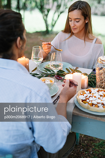 Couple having a romantic candelight meal in garden - p300m2068917 by Alberto Bogo
