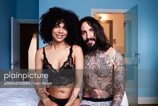 Portrait of smiling young couple sitting on bed - p300m2103594 by Ivan Gener