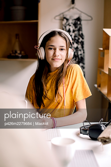 Portrait of smiling girl in yellow T-shirt sitting at desk - p426m2279684 by Maskot