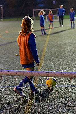 Girl soccer player practicing on field at night - p1023m2035224 by Paul Bradbury
