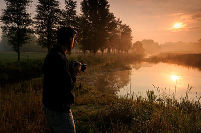 A photographer at the Regge river in the morning light - p1144m943982 by Ernst Kremers