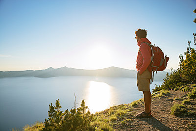 Hiker with backpack standing on mountain at Crater Lake National Park during sunny day - p1166m1415113 by Cavan Images