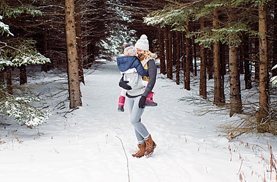 Happy mother carrying daughter while standing in forest during winter - p1166m1554523 by Cavan Images