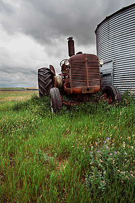 Tractor parked amidst plants on field against cloudy sky - p1166m2024947 by Cavan Social