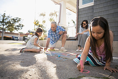 Multi-generation family drawing with sidewalk chalk in driveway - p1192m1418540 by Hero Images