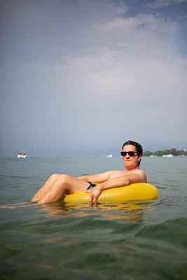 Mann im Schwimmring auf See - p1308m2247515 von felice douglas