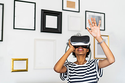 Young woman with VR glasses at home - p300m2143778 by Giorgio Fochesato
