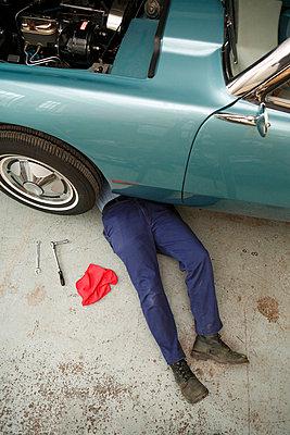 Mechanic laying under car - p3722396 by James Godman