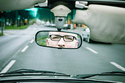 Reflection of young man wearing glasses driving car in rearview mirror - p429m801644 by sah