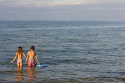 Brother and sister paddling in sea - p429m929470f by Richard Lewisohn