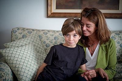 Caucasian grandmother and grandson sitting on sofa - p555m1306026 by Alberto Guglielmi