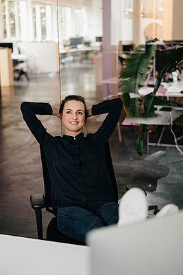 Junge Geschäftsfrau im Büro träumt vor sich hin - p586m1451941 von Kniel Synnatzschke