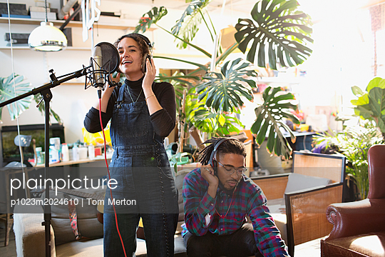 Young man and woman recording music in apartment, singing into microphone - p1023m2024610 by Tom Merton