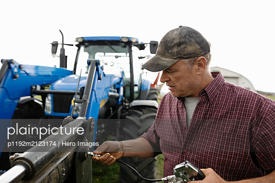 Male farmer fixing tractor - p1192m2123174 by Hero Images