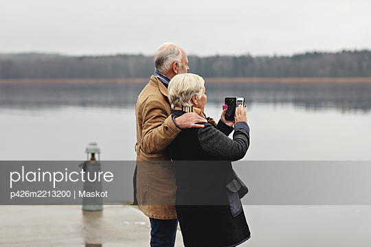 Senior couple photographing while standing by lake against clear sky - p426m2213200 by Maskot