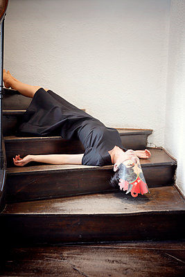 Woman with black dress lying on staircase - p1105m2244904 by Virginie Plauchut
