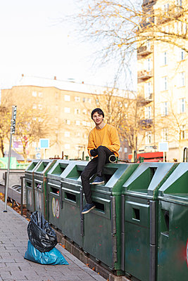 Portrait of smiling male volunteer sitting on garbage can - p426m2213237 by Maskot