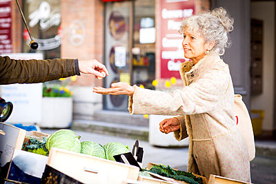 Mature female shopper buying vegetables at local french market - p429m1418342 by JAG IMAGES
