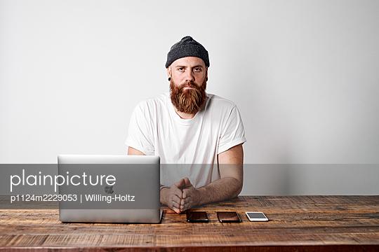 Mann am Schreibtisch mit Laptop und Smartphones - p1124m2229053 von Willing-Holtz