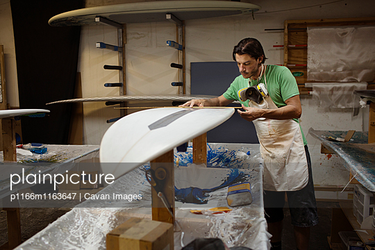 Worker measuring surfboard in workshop - p1166m1163647 by Cavan Images