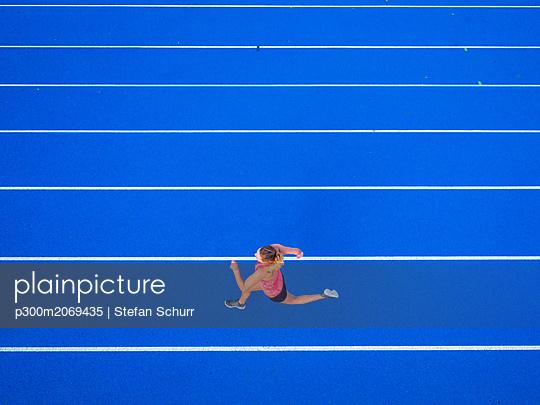 Top view of female runner on tartan track - p300m2069435 by Stefan Schurr