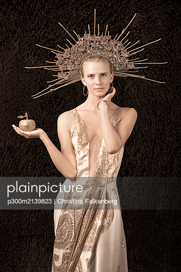 Young woman wearing dress with low neckline and headpiece, holding an apple - p300m2139823 by Christina Falkenberg