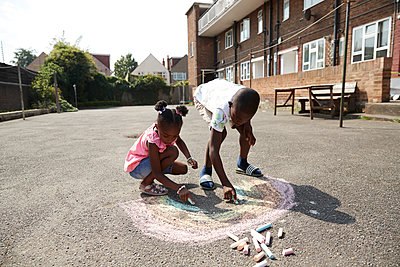 Brother and sister drawing rainbow with sidewalk chalk on pavement - p1023m2238493 by Himalayan Pics