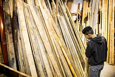 Young man standing next to a stack of wooden planks in a warehouse. - p1100m1575721 by Mint Images