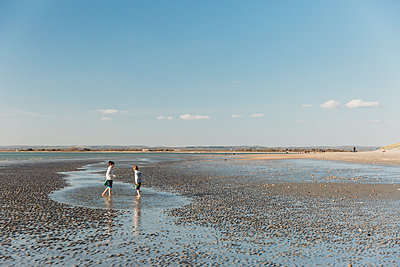 Two brothers paddling and playing on beach at low tide - p1166m2130798 by Cavan Images