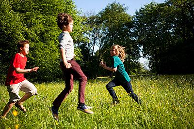 Drei Jungen toben im Park - p1195m1138148 von Kathrin Brunnhofer